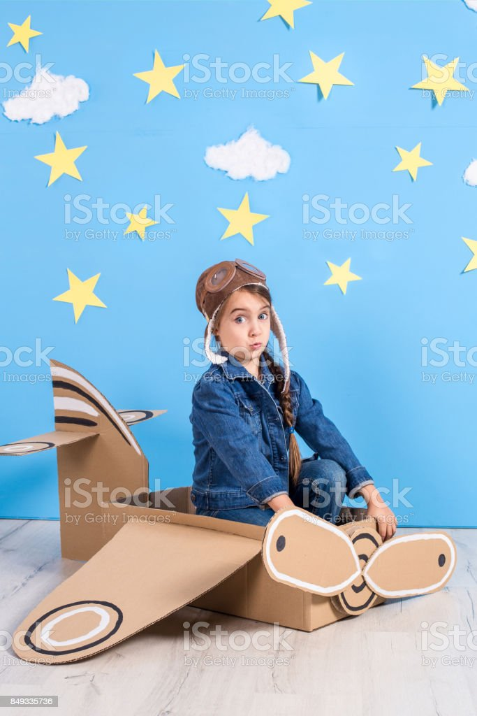 Little child girl in a pilot\'s costume is playing and dreaming of...