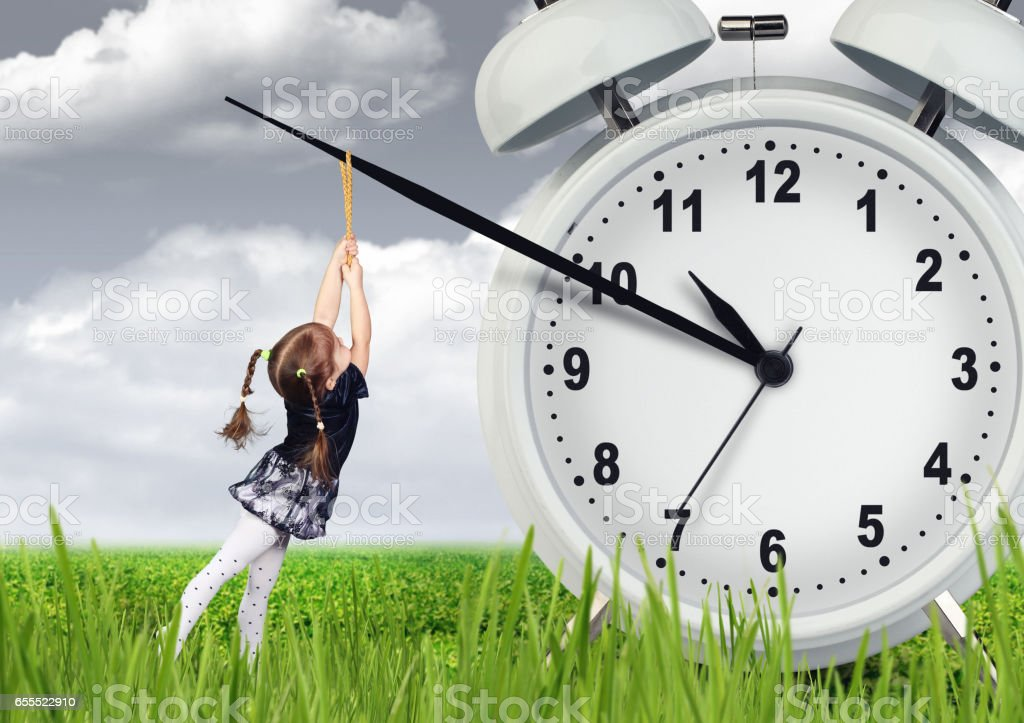 Little child girl pulling hand clock, time stop concept stock photo