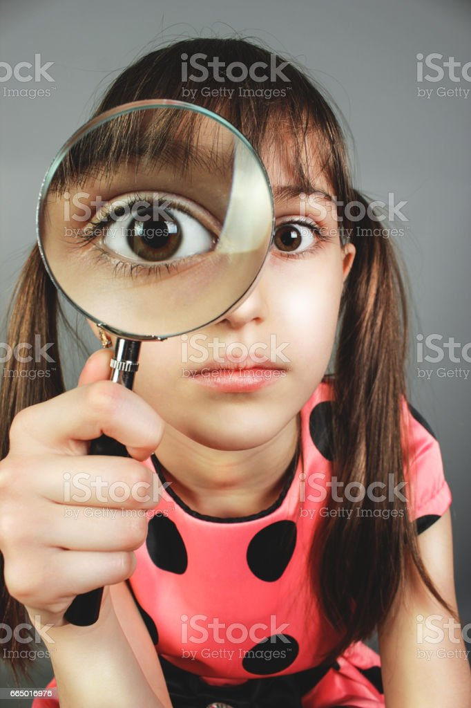 little child girl searching  with magnifying glass stock photo