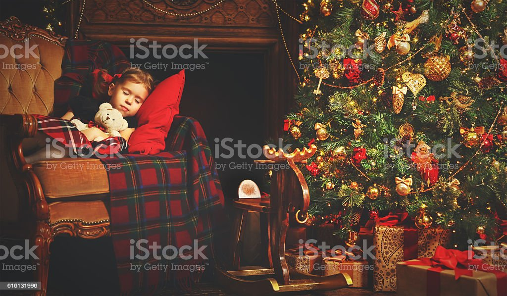 little child girl sleeping near a Christmas tree stock photo