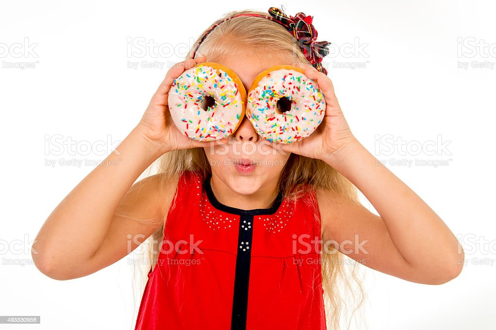 little child happy playing with sugar donuts as her eyes stock photo