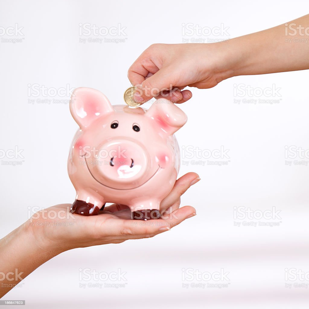 Little child inserting coin into a piggy bank royalty-free stock photo
