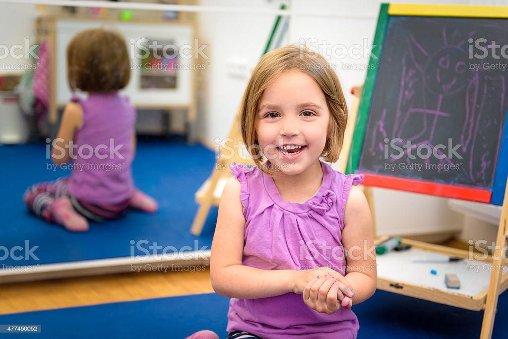 Little child is drawing with color chalk on the chalk stock photo