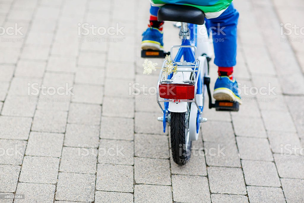Little child on first bike. Hands of kid. stock photo