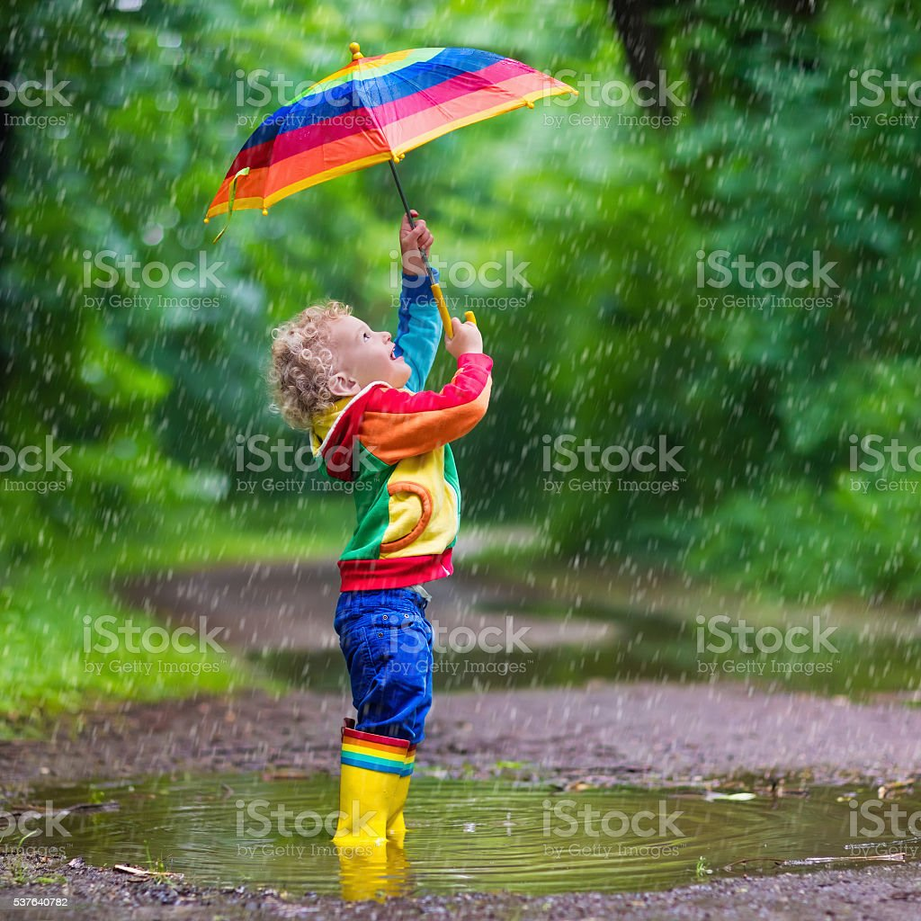 Little child playing in the rain stock photo