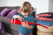 little child playing red guitar