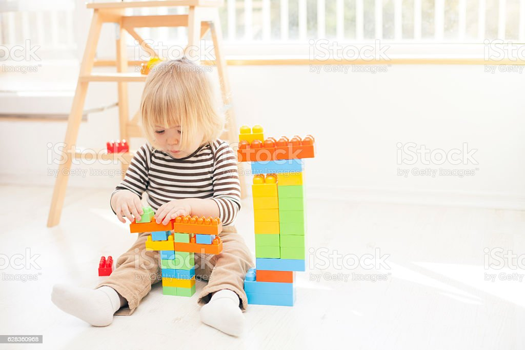 Little child playing with colorful plastic blocks stock photo