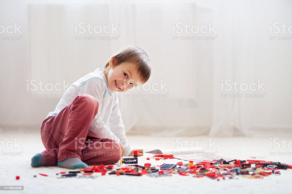 Little child playing with lots of colorful plastic blocks indoor stock photo