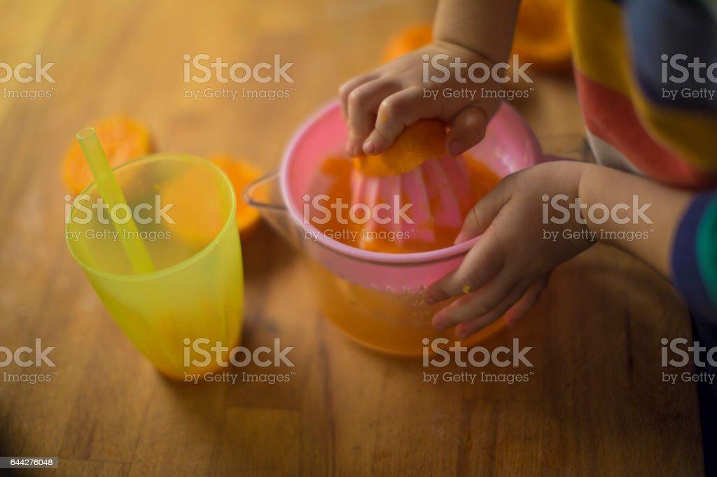 Little child preparing fresh homemade orange juice stock photo