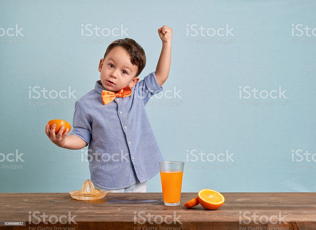 Little child preparing homemade orange juice stock photo