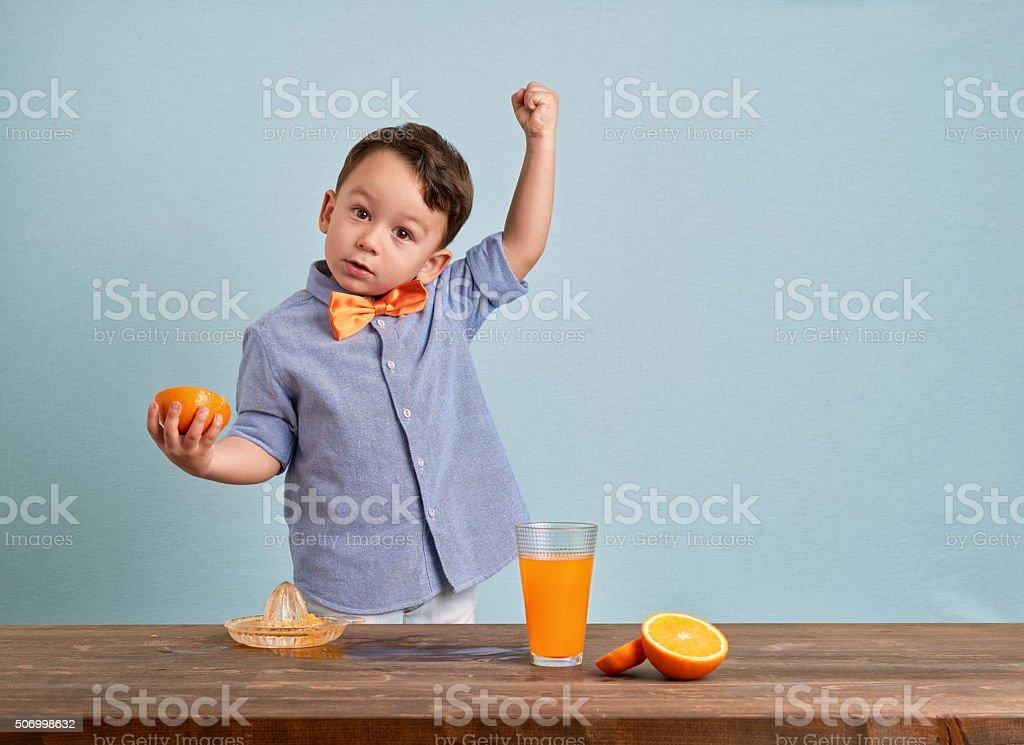 Little child preparing homemade orange juice stock photo