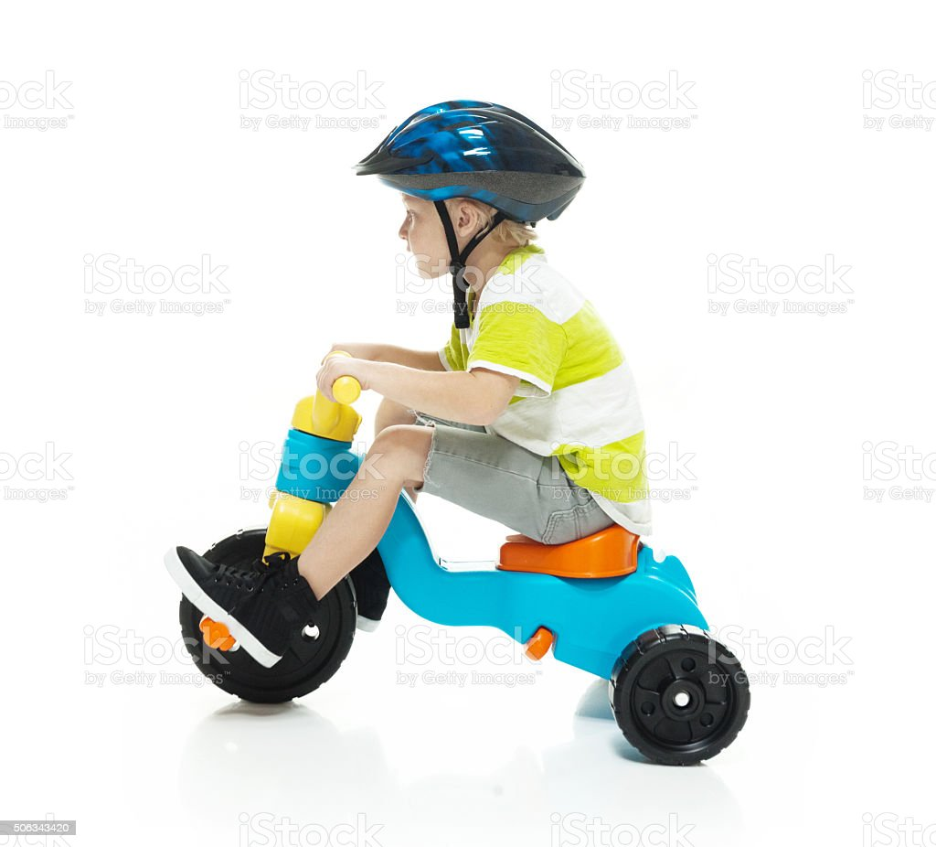 Little child riding tricycle stock photo