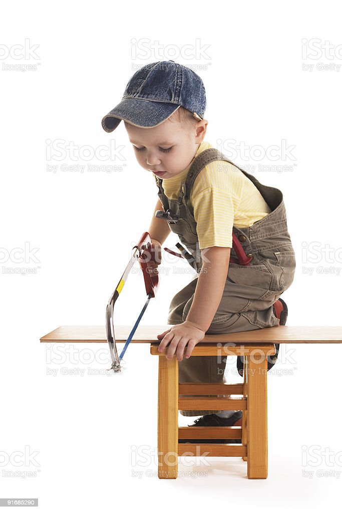 Little child saws plank by handsaw royalty-free stock photo