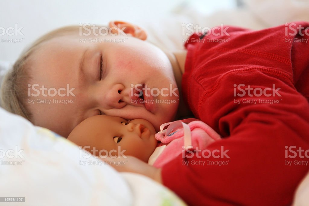 Little child sleeping with doll stock photo
