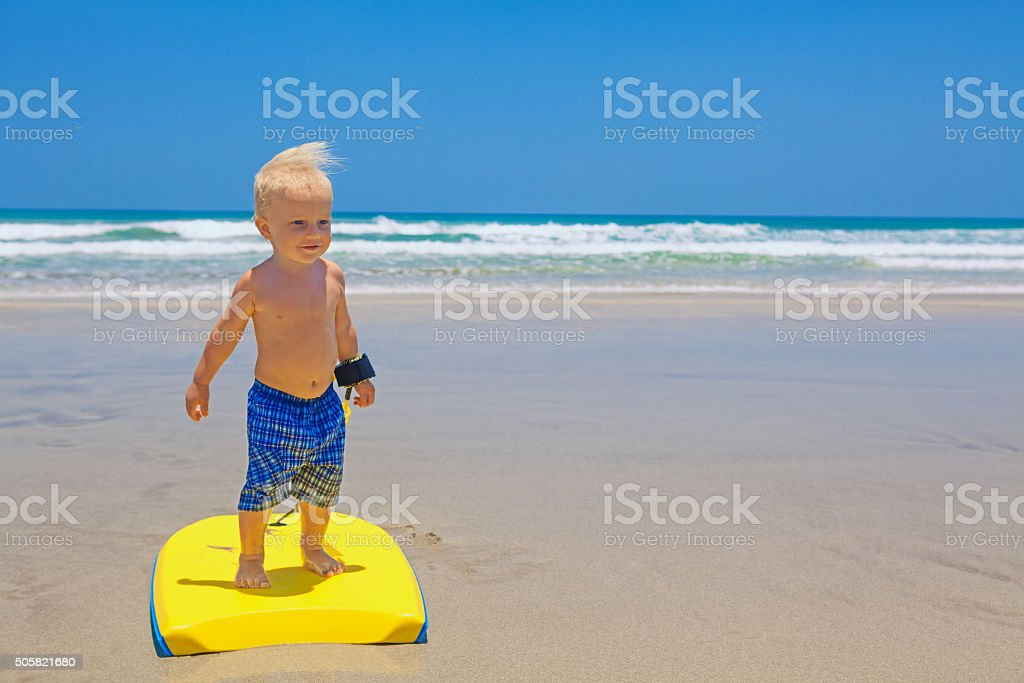 Little child swimming with bodyboard on the sea sand beach stock photo