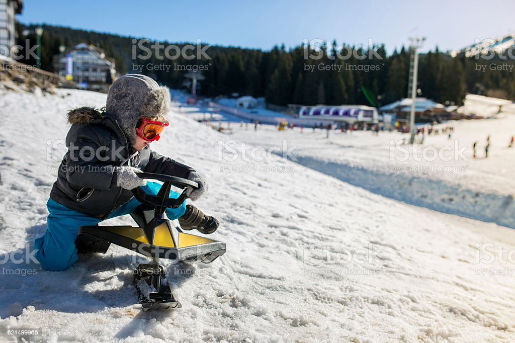 Little child trying to sit on a snowmobile toy. stock photo