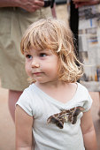 little child with big butterfly on her shirt
