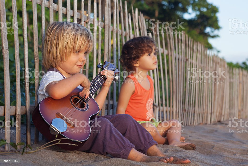 Little children have fun on sunset tropical beach. stock photo