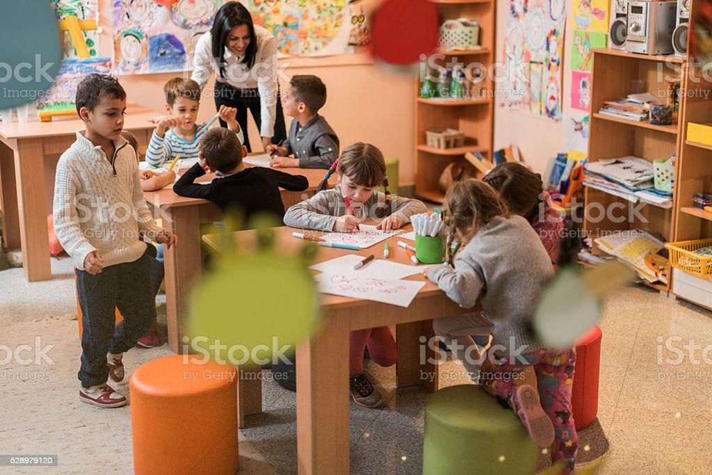 Little children having an art class in a preschool. stock photo