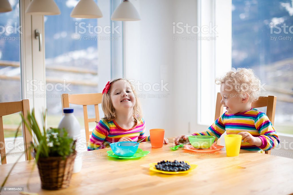 Little children having breakfast in sunny kitchen stock photo
