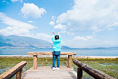 Little Chinese boy raising his hands while standing on lakeside