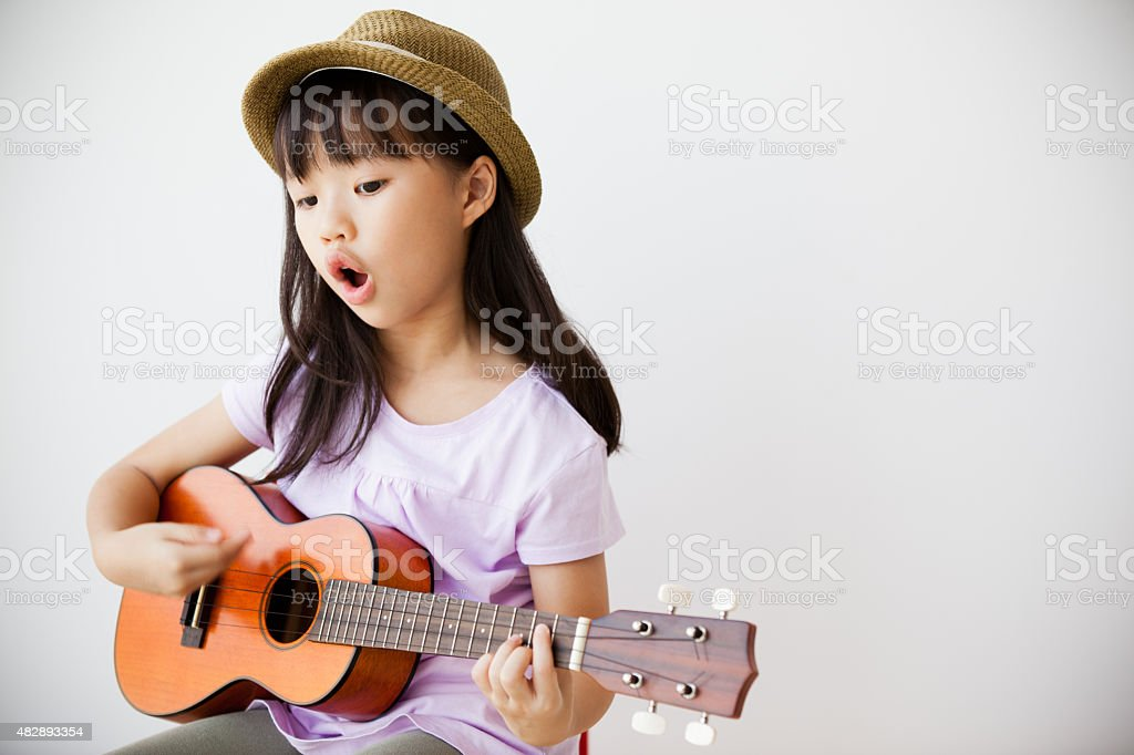 Little Chinese Girl Singing and Playing Ukulele stock photo
