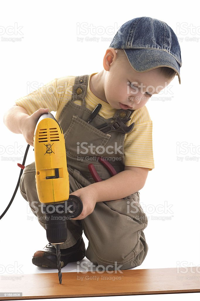 Little construction boy drills by drill royalty-free stock photo