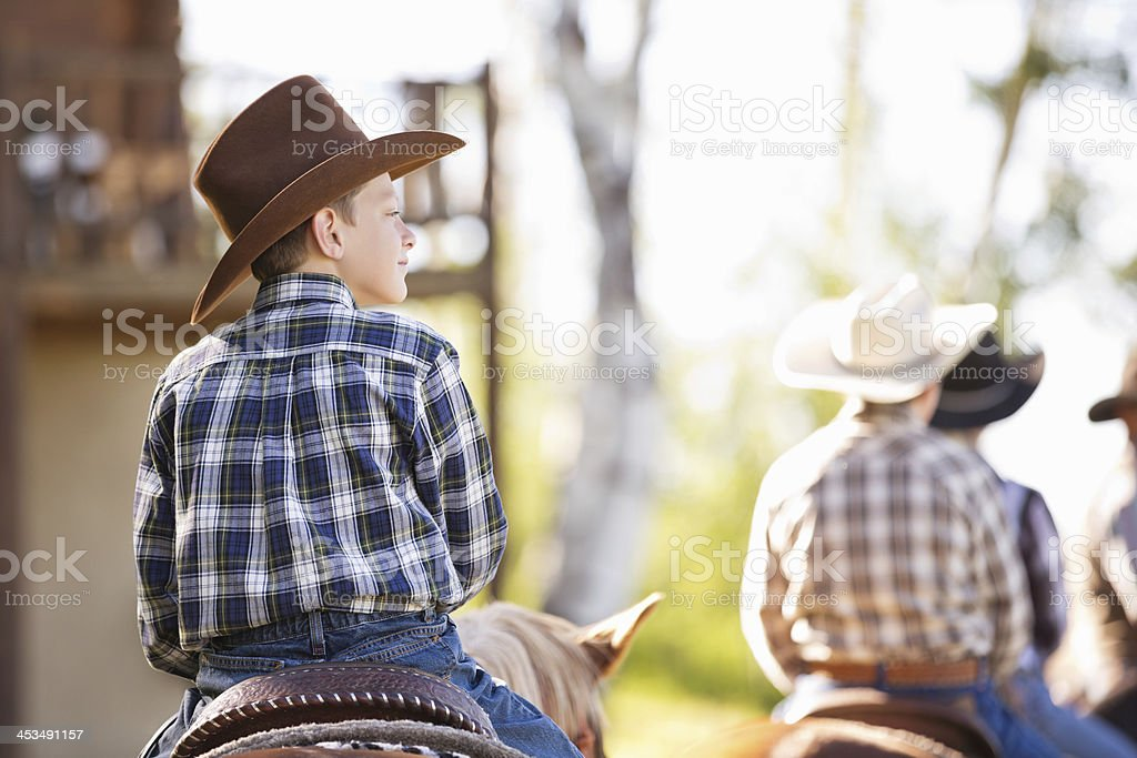 Little cowboy riding horse during ranch trail ride royalty-free stock photo