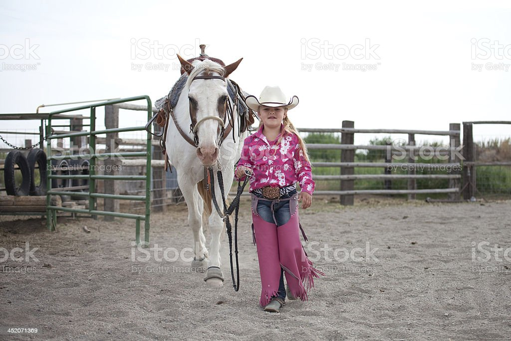 Little Cowgirl Walking with Horse royalty-free stock photo