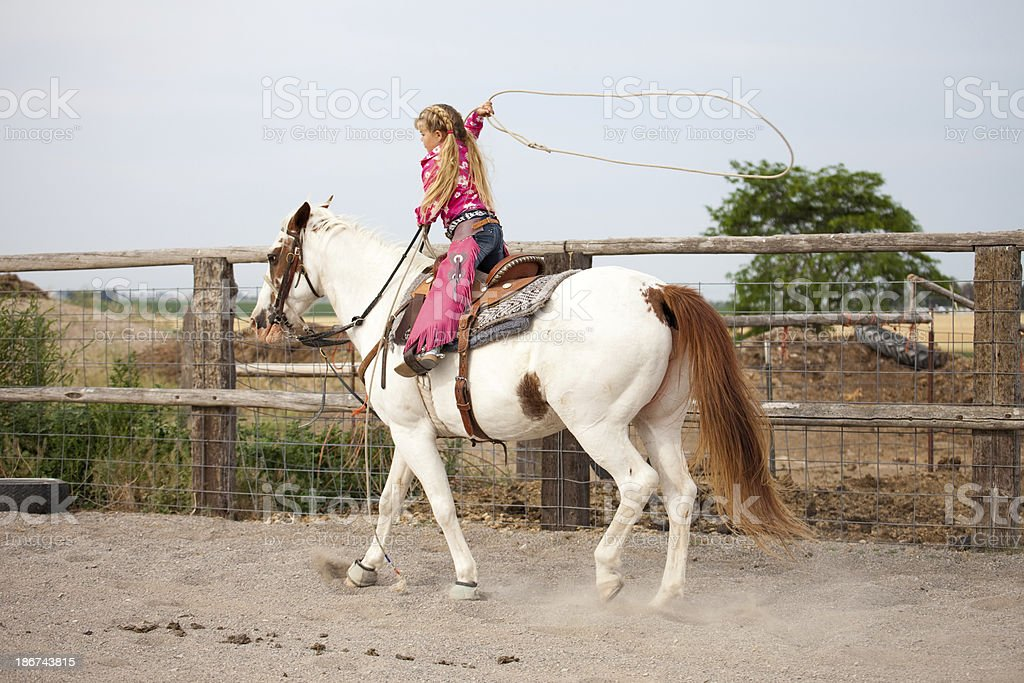 Little Cowgirl Wearing Pink Riding Horse Swinging Lasso royalty-free stock photo
