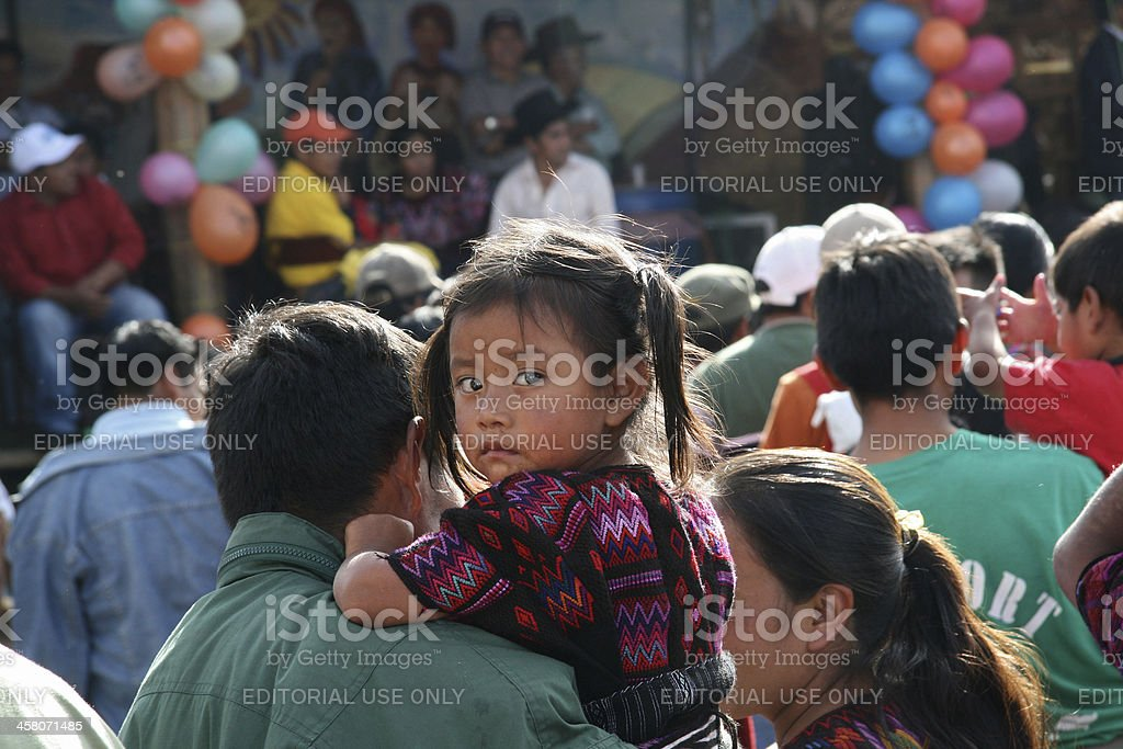 Little curious Mayan girl with her parents in Chichicastenango, Guatemala stock photo
