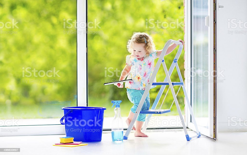 Little curly girl washing a window stock photo
