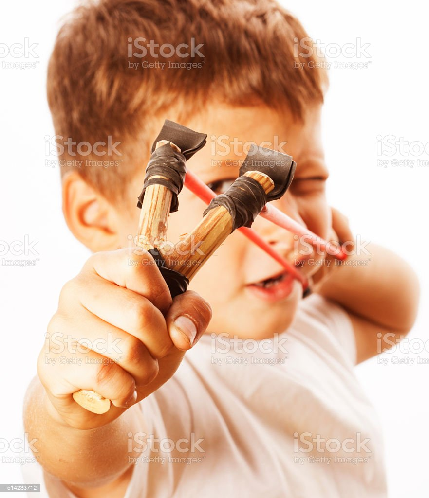 little cute angry real boy with slingshot isolated stock photo