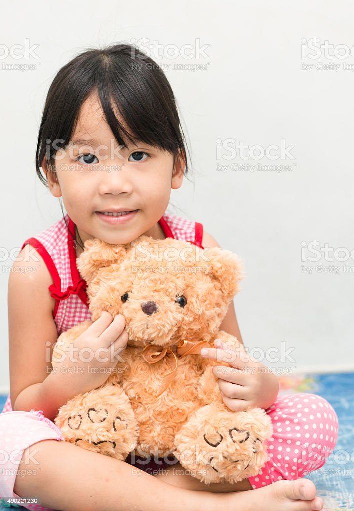 Little cute asian gril hug teddy bear stock photo