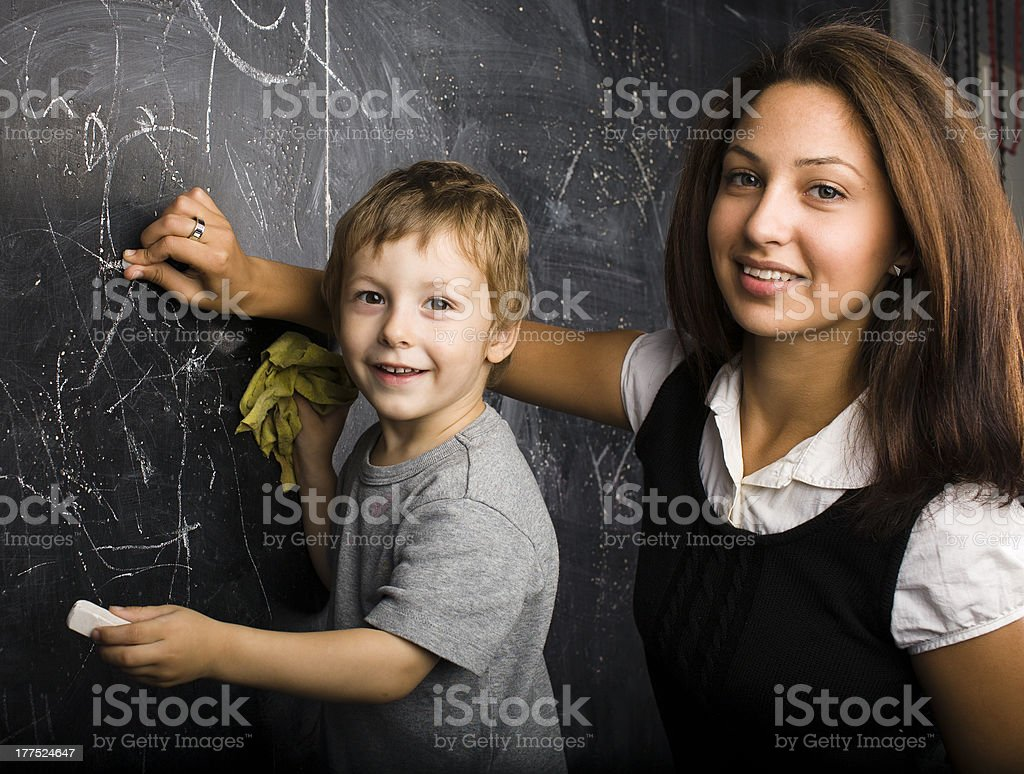 little cute boy in classroom with teacher royalty-free stock photo