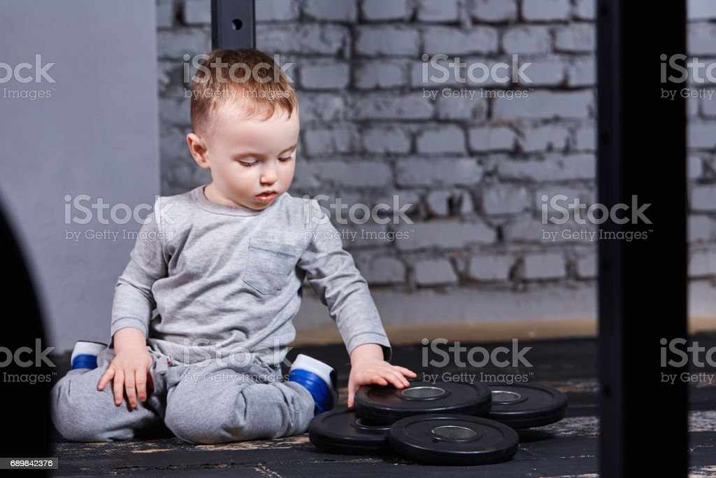 Little cute boy in sportwear sitting on the floor at the gym and looking on the barbell against brick wall. stock photo