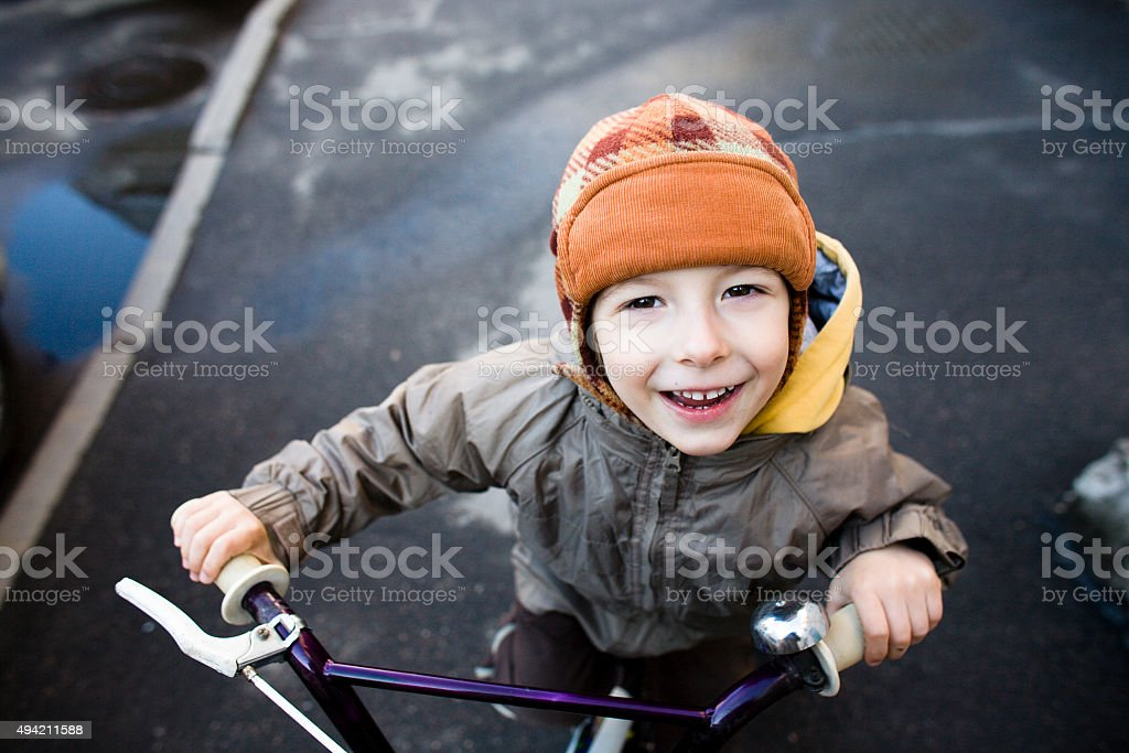 little cute boy on bicycle smiling close up stock photo