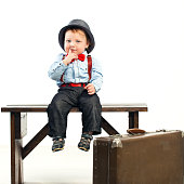 Little cute boy sitting with luggage. Children Travel Concept