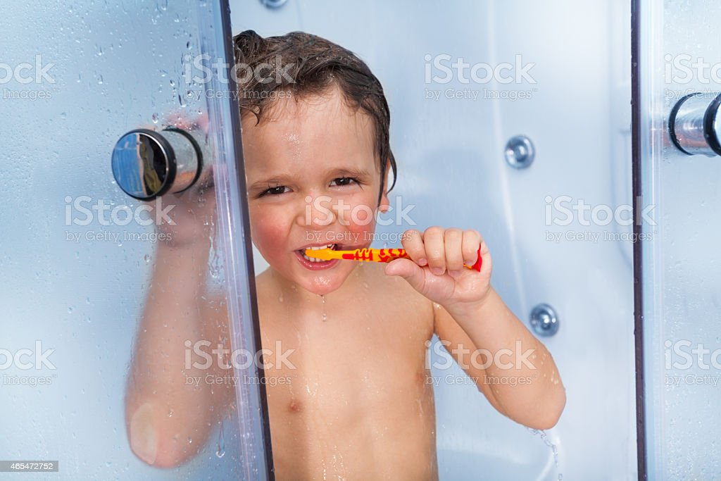 Little cute boy use toothbrush in shower cabin stock photo