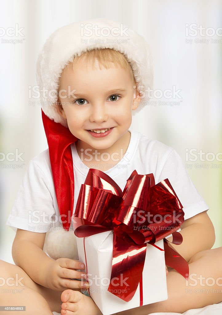 little cute child boy in a Christmas hat with gift royalty-free stock photo