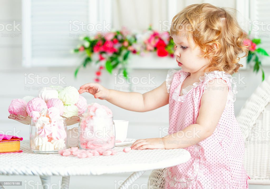 Little cute curly girl in pink dress eat different sweets. stock photo