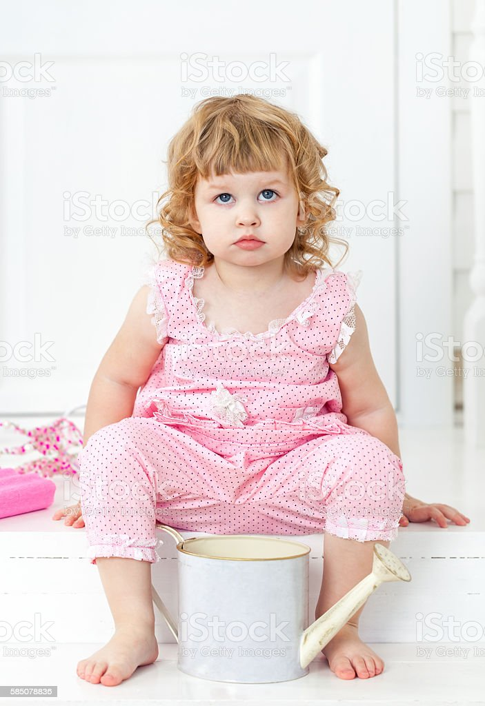 Little cute curly girl sitting on white porch Provence style stock photo