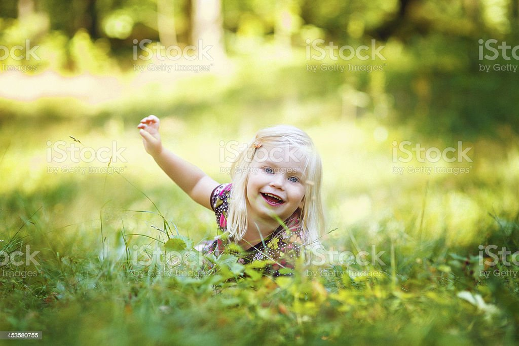 Little cute gir laying on the grass royalty-free stock photo