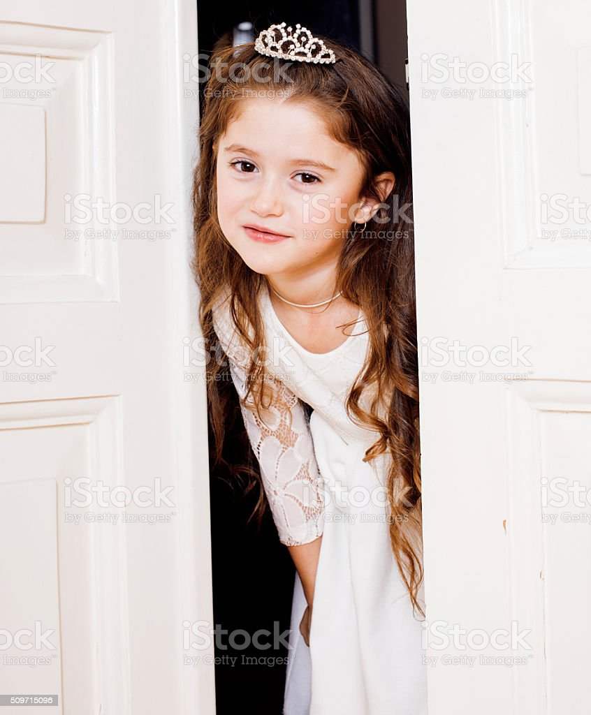 little cute girl at home, opening door well-dressed in stock photo