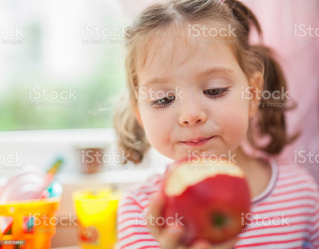 little cute girl eating apple stock photo