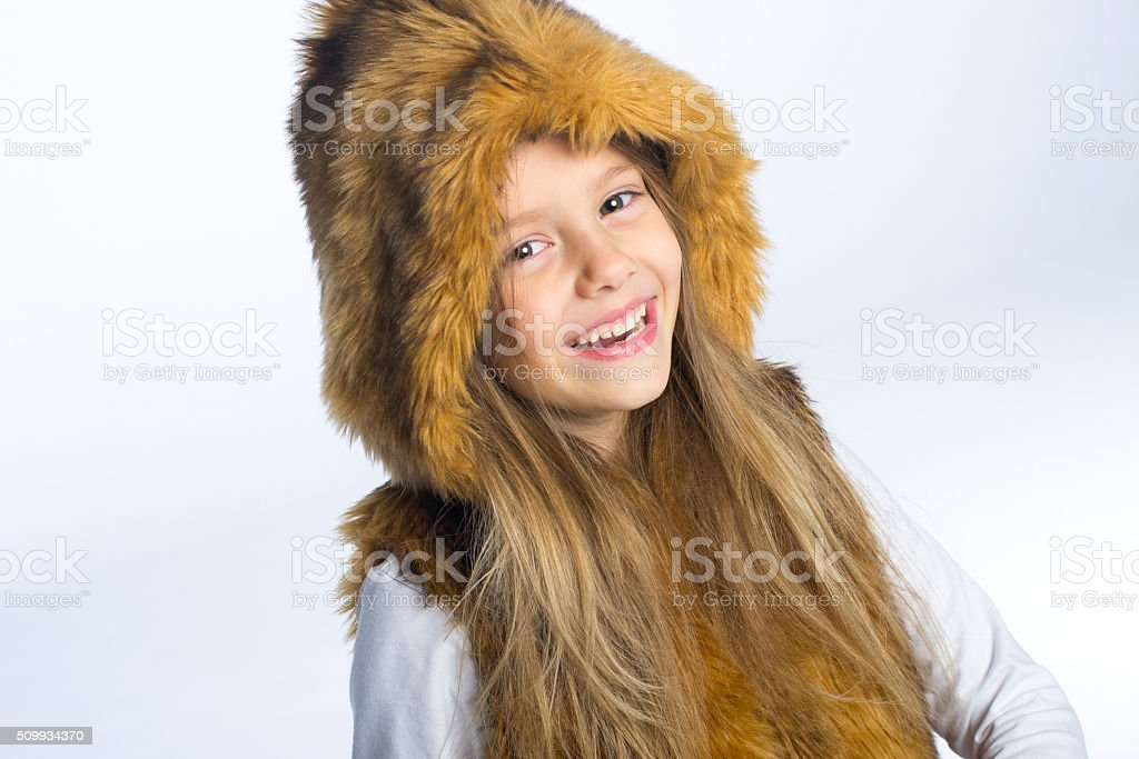 Little cute girl in a fur hooded vest stock photo