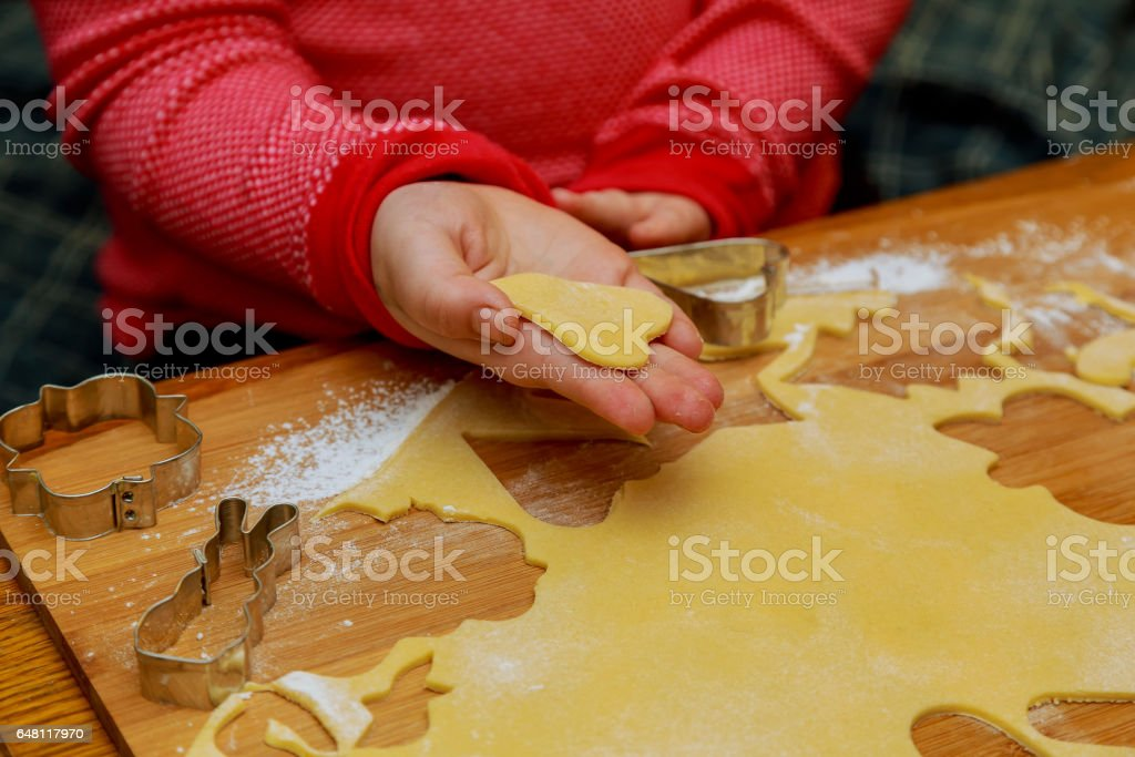 little cute girl puts on baking cookies stock photo