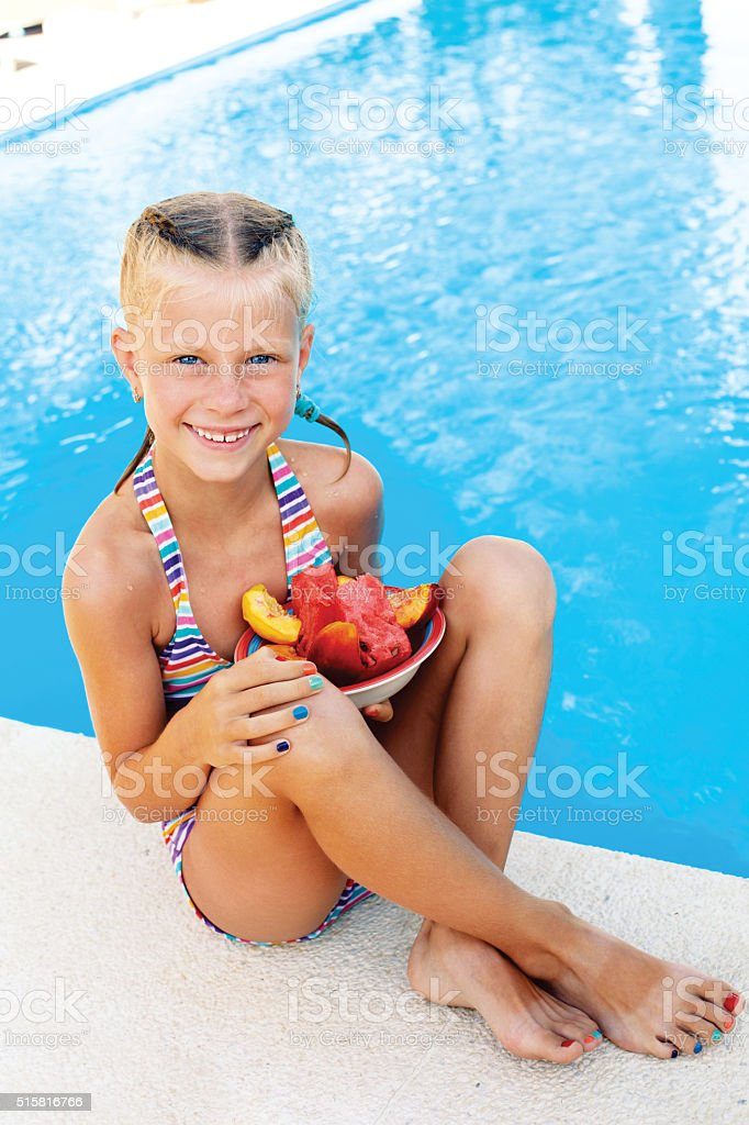 Little cute girl sitting beside the pool. Summer. stock photo