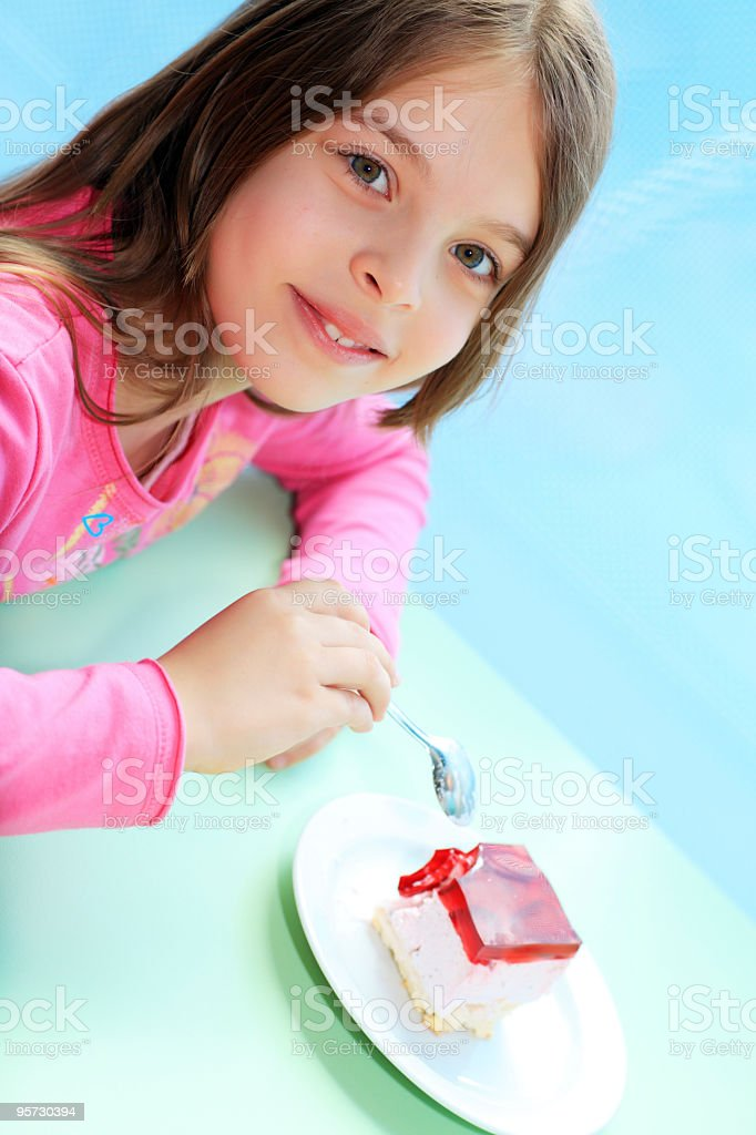 Little cute girl sitting in a cafe eating cake. stock photo