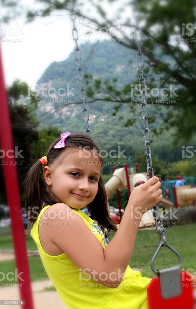 Little cute girl with ponytails on swing in mountain area. stock photo